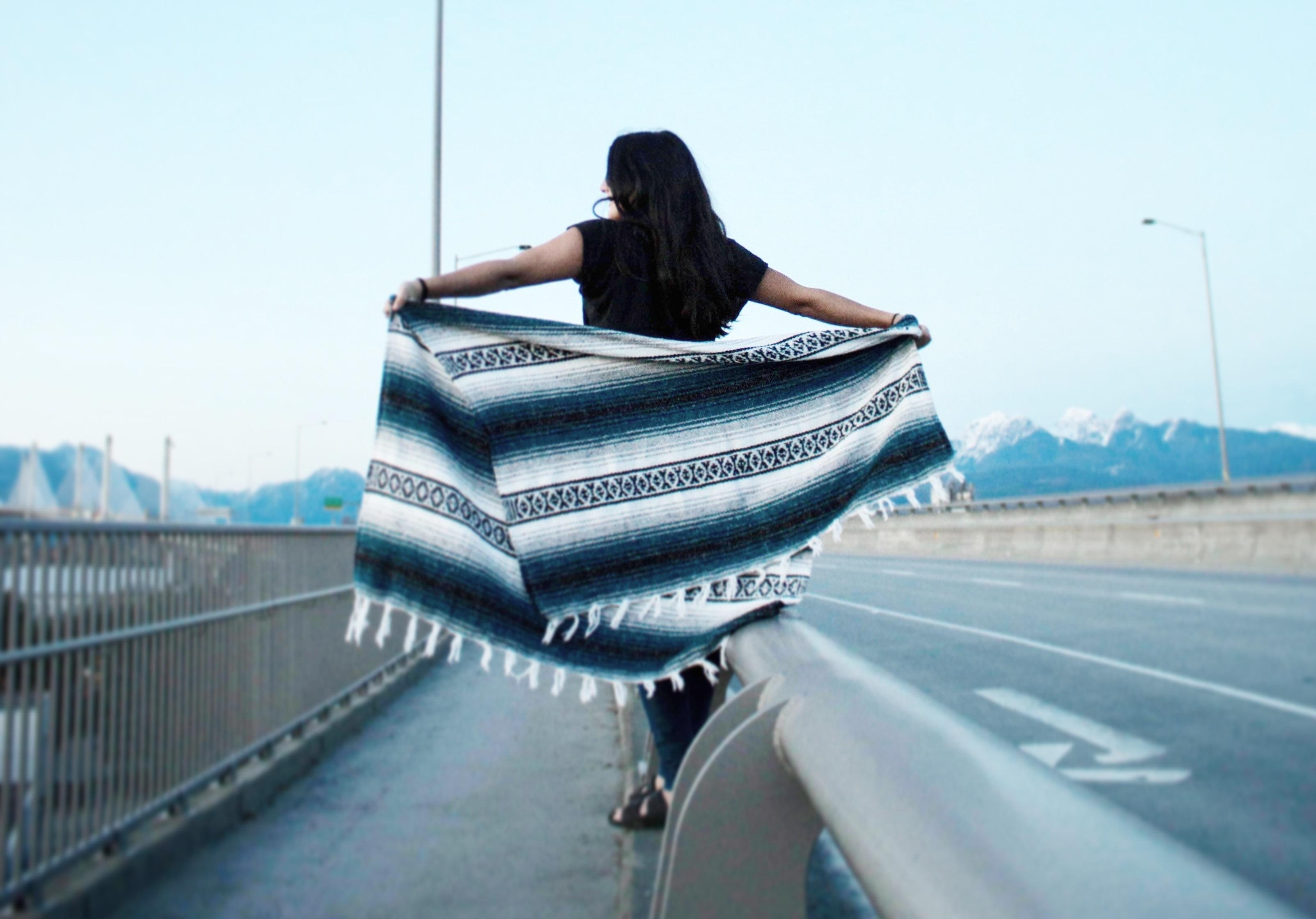 happy girl walking on street holding blanket
