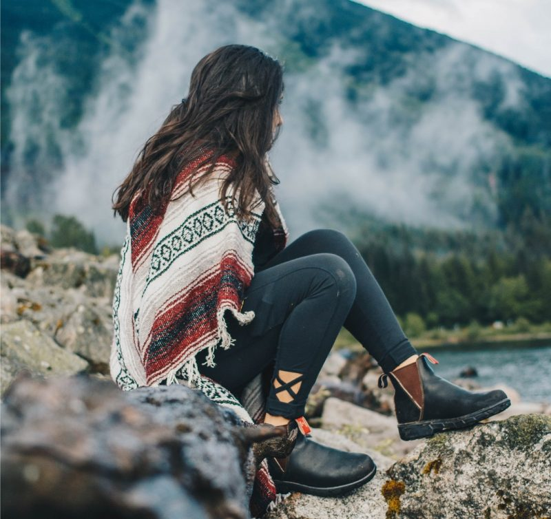 girl with blanket sitting on a mountain