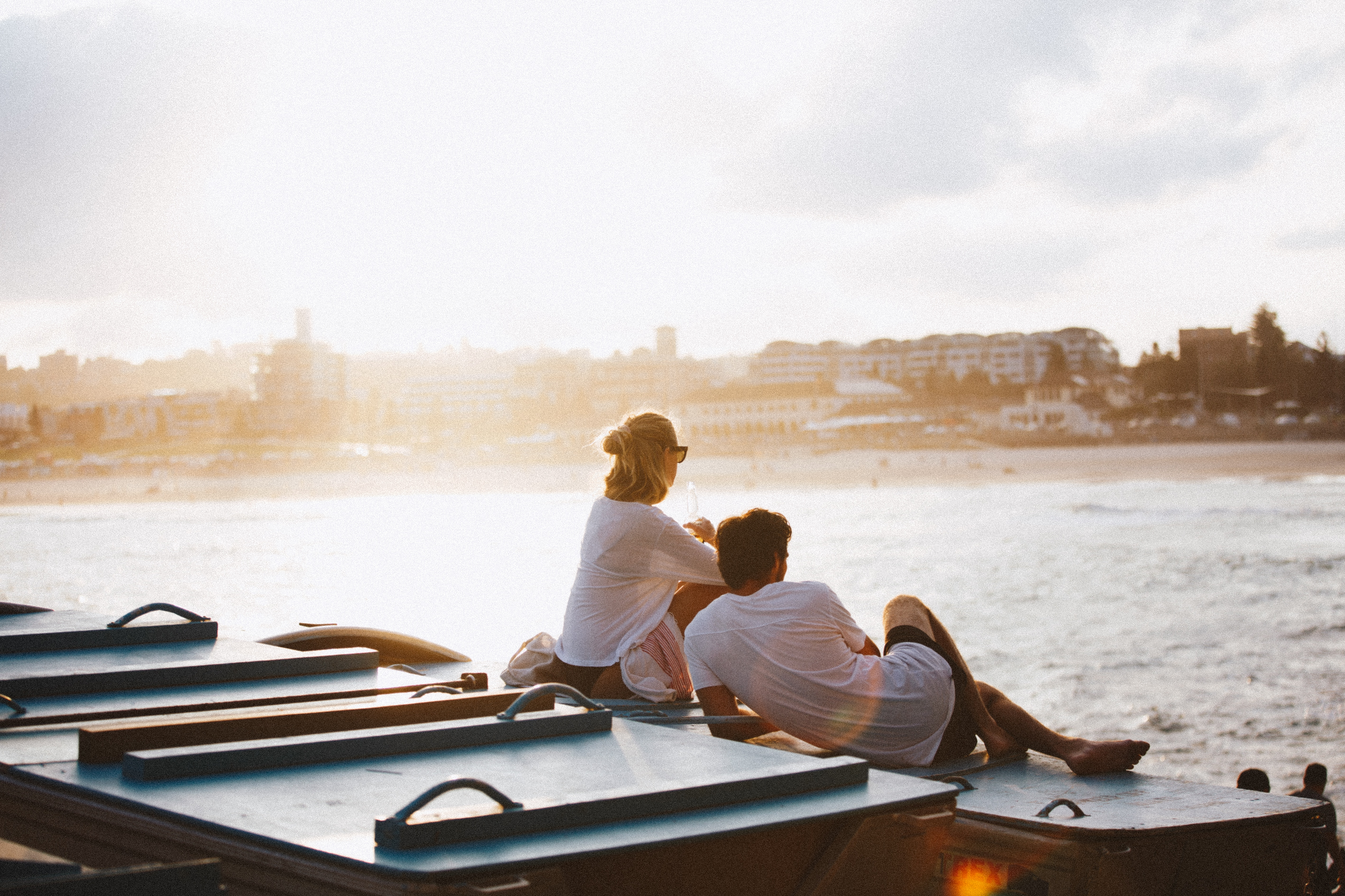 couple leaning on one another by water