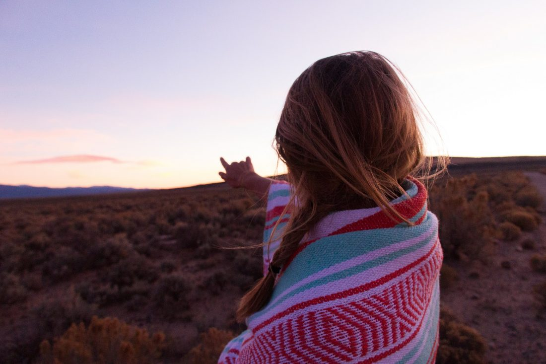 in christ you are victorious, girl pointing at sunset