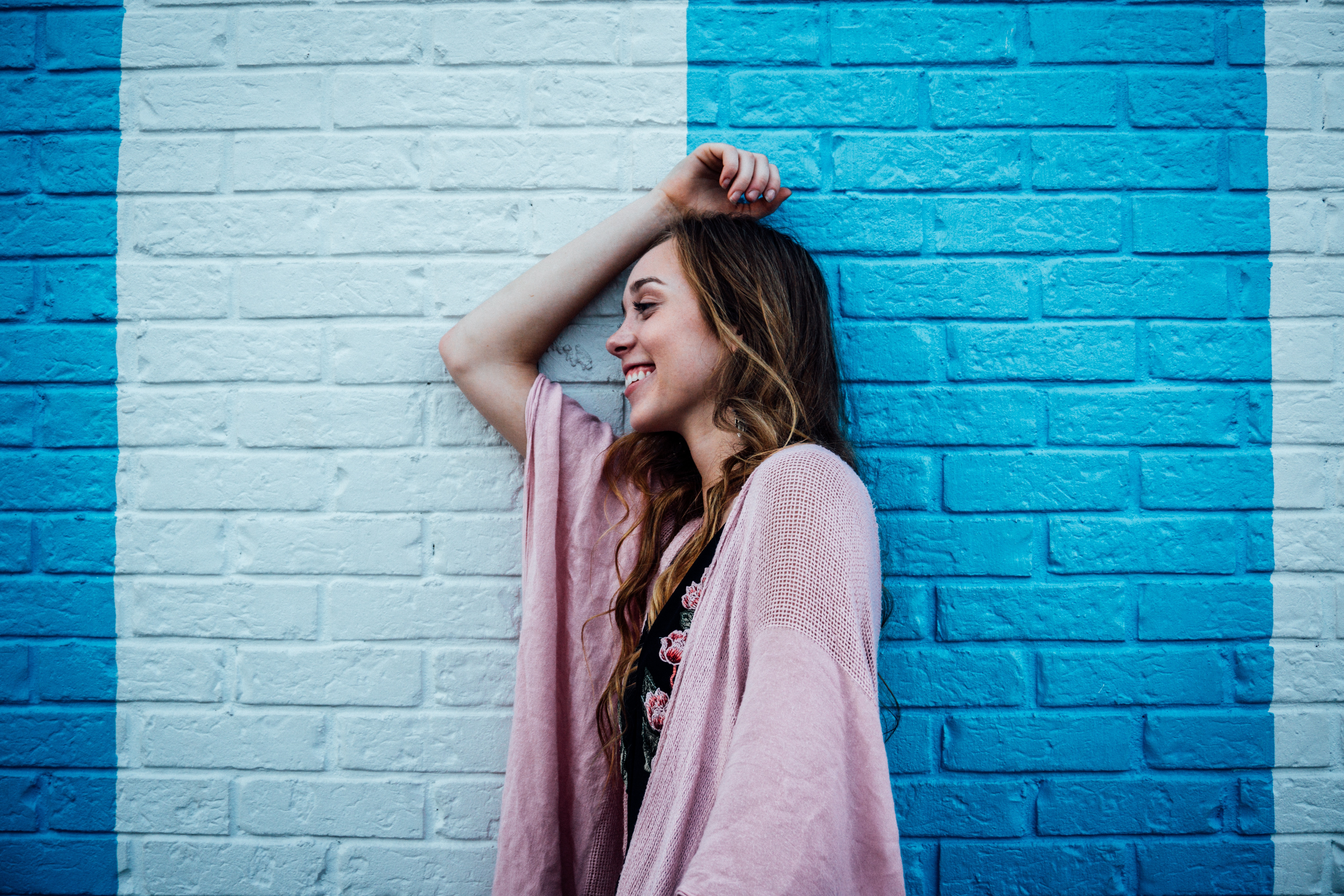 girl smiling by blue brick wall