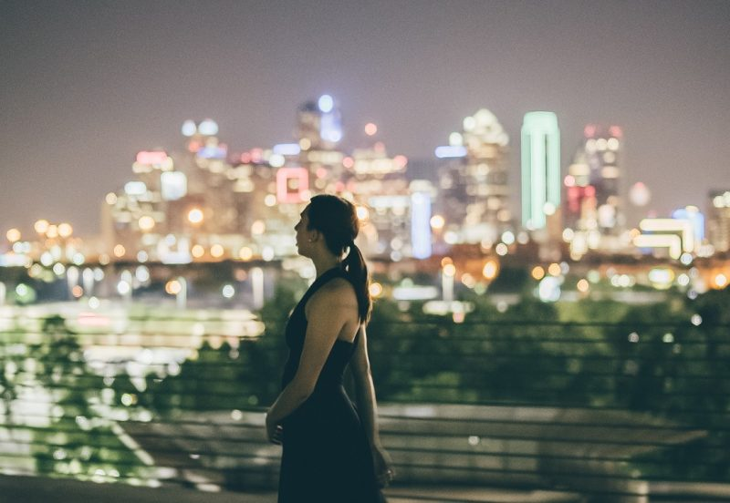 girl looking at night skyline, supposed to be lost