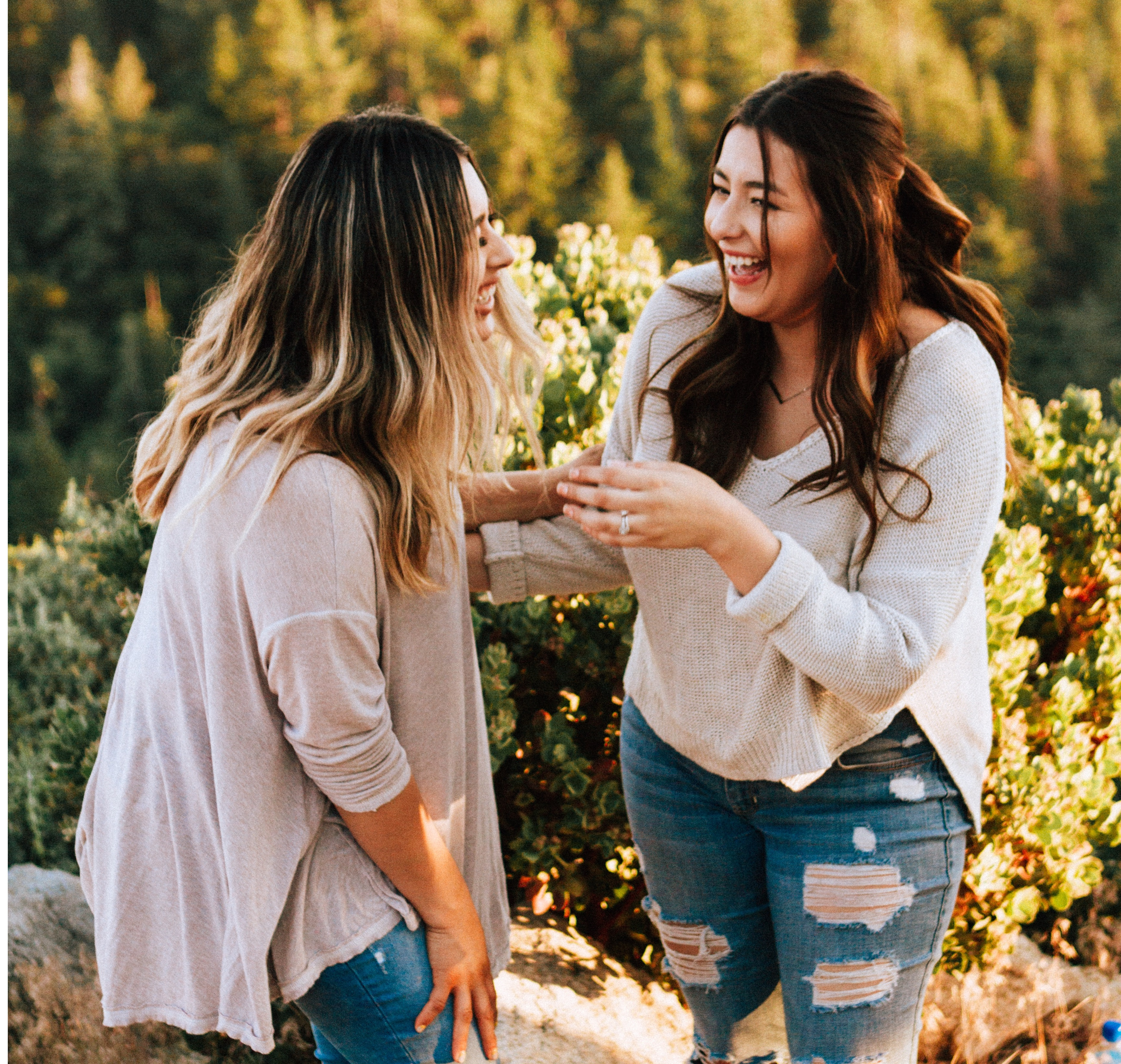 girls laughing and leaning towards each other by trees