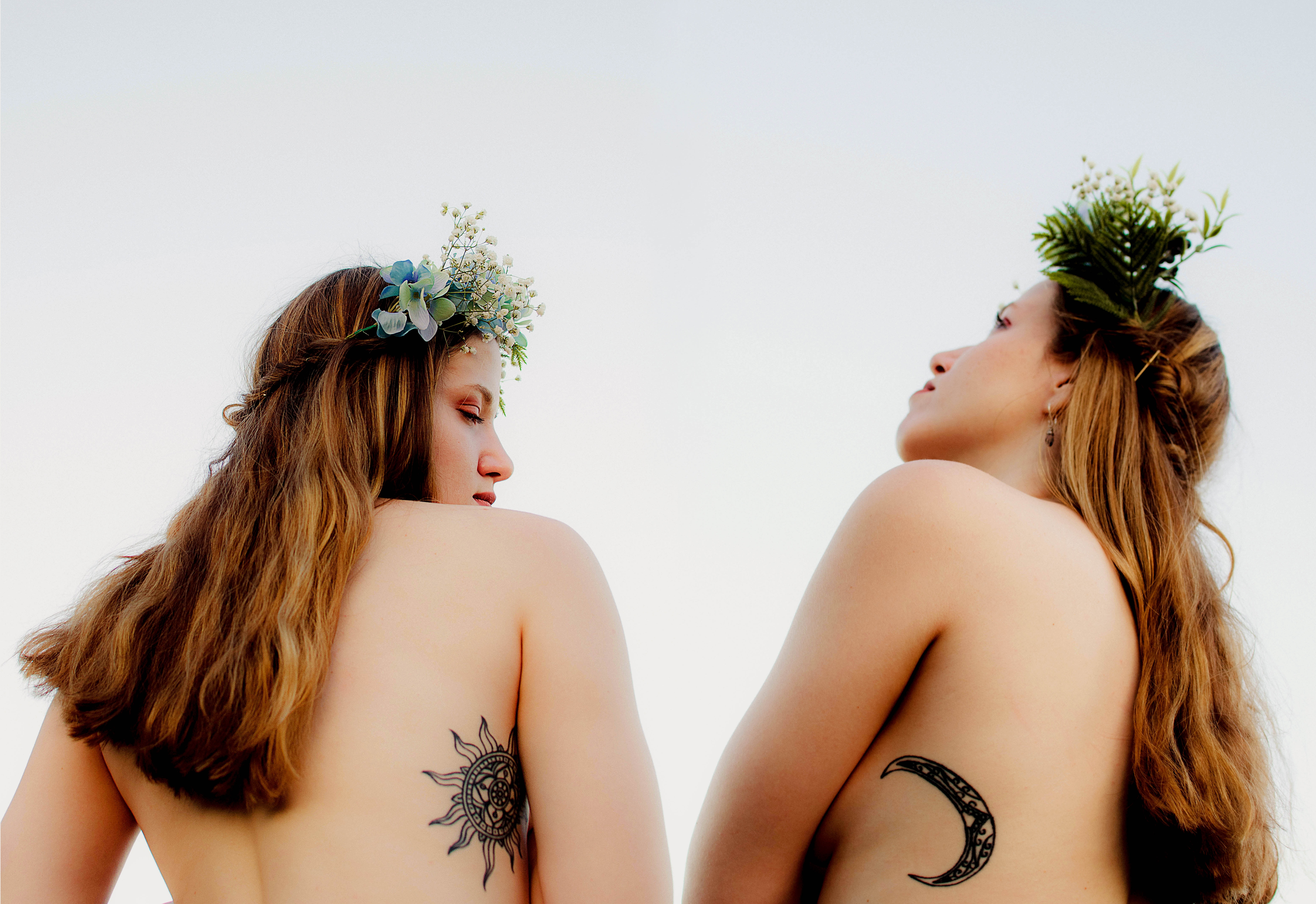 two women with tattoos smiling at the sky