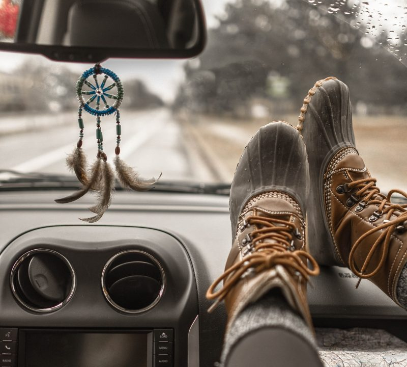 feet on dashboard looking at road, leaving everything behind