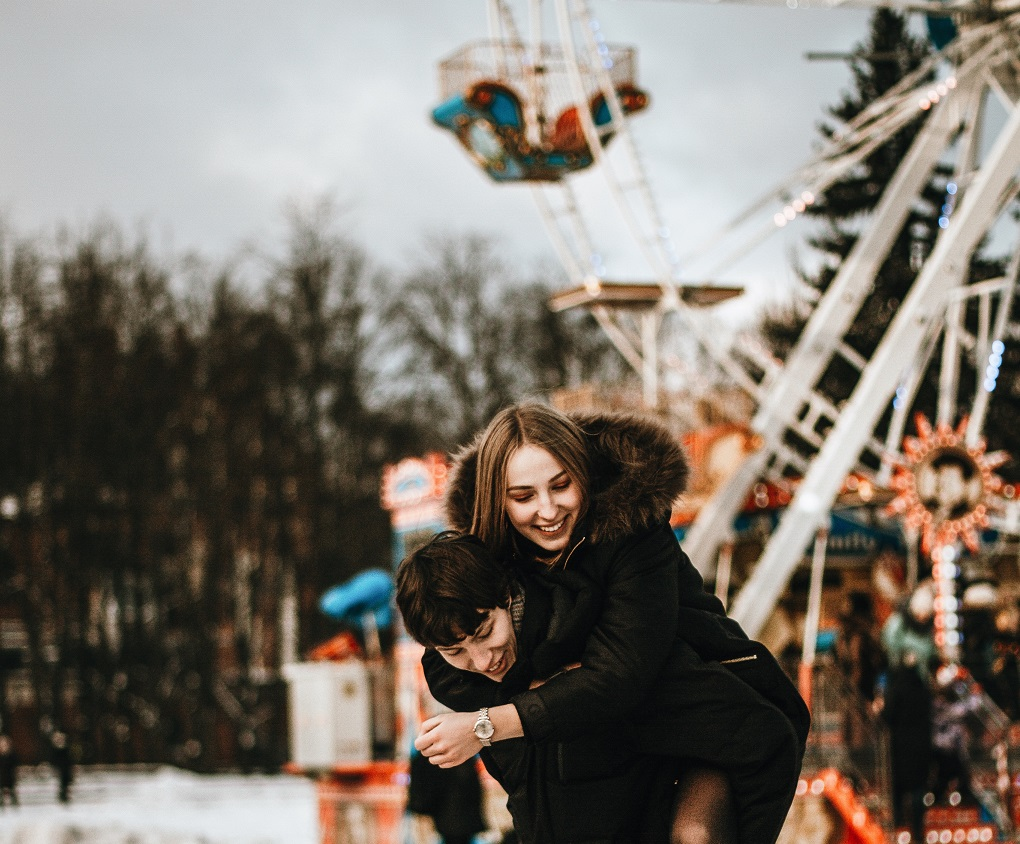 happy couple piggyback at amusement park, what love really is