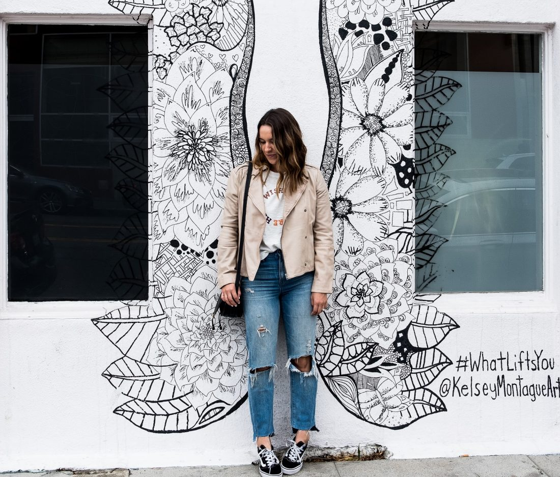 happy woman posing in front of painted wall, find your wings