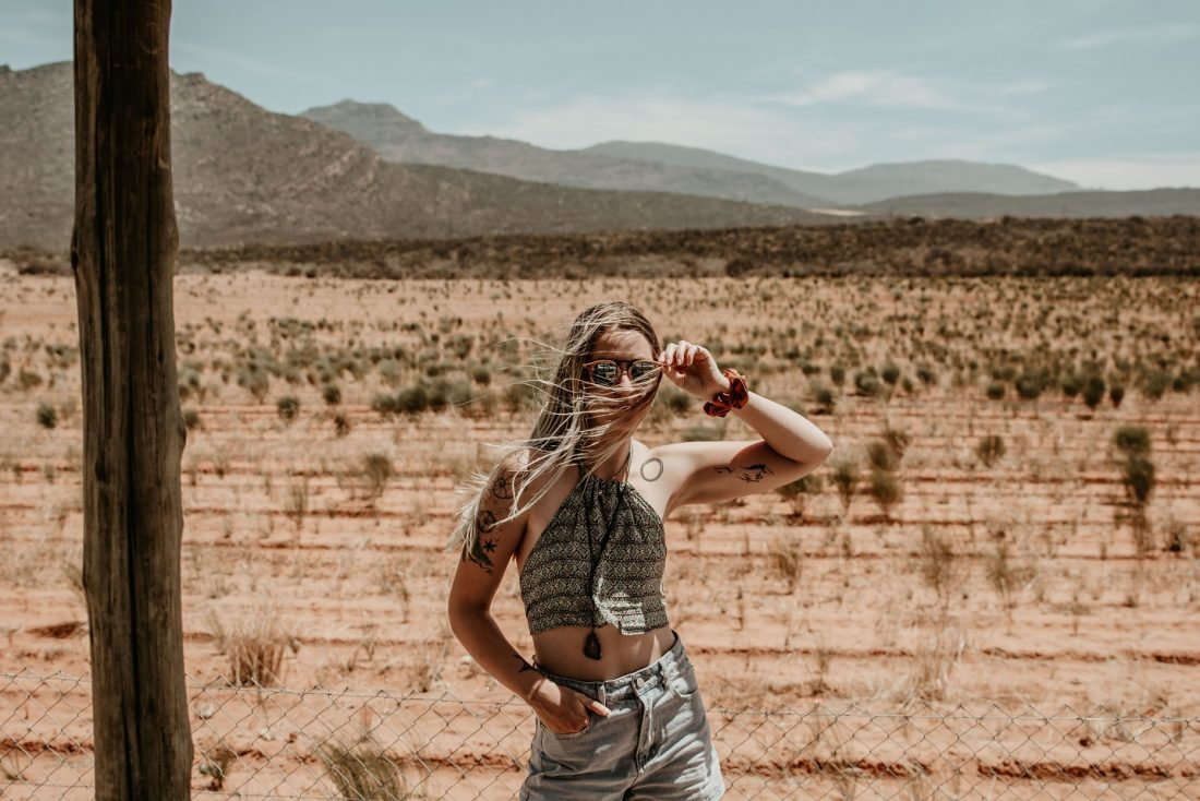 woman with arm up standing in front of desert, let go