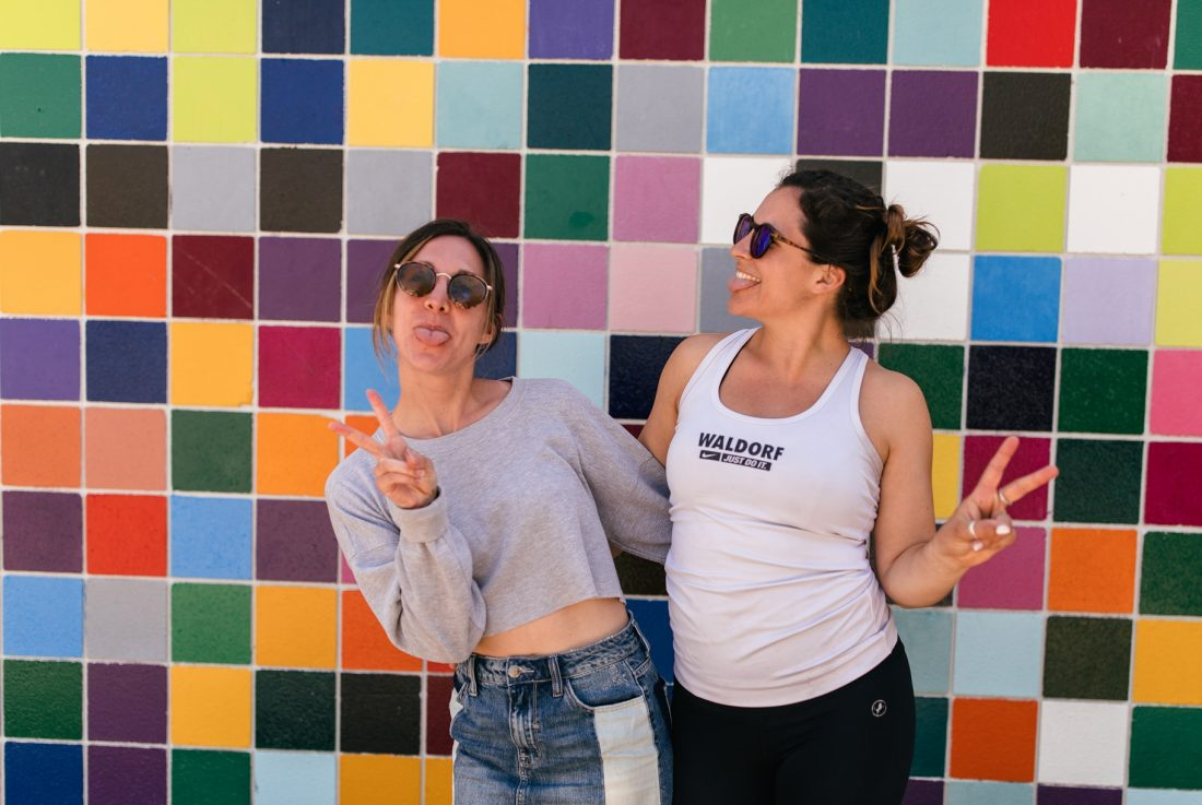 happy girls with peace signs in front of colorful wall